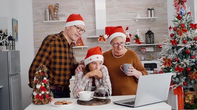 Avós com neta cumprimentando amigos remotos durante reunião de videochamada online