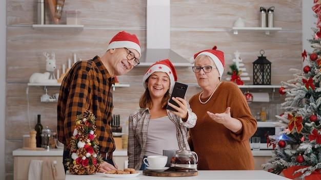 Avós com neta cumprimentando mãe remota comemorando feriado de natal
