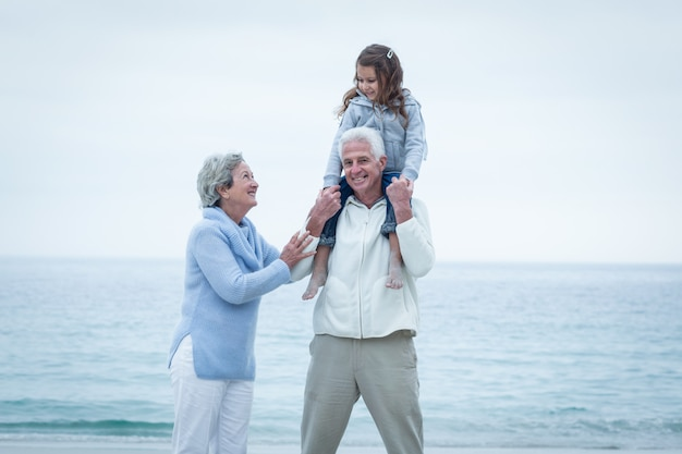 Avós com neta desfrutando na praia