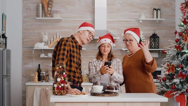 Avós com neto usando chapéu de papai noel cumprimentando amigos remotos durante videochamada online