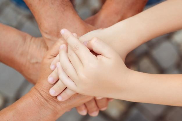 Avós com o neto de mãos dadas, vista superior. conceito de família, cuidados e suporte. o conceito de cuidar amadurece juntos.