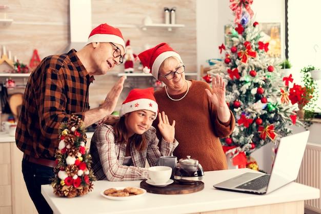 Avós comemorando o natal com a sobrinha em casa acenando para uma webcam conversando com parentes