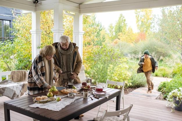 Avós contemporâneos em trajes casuais aconchegantes, inclinando-se sobre a mesa enquanto o servem antes do jantar com o neto correndo até eles