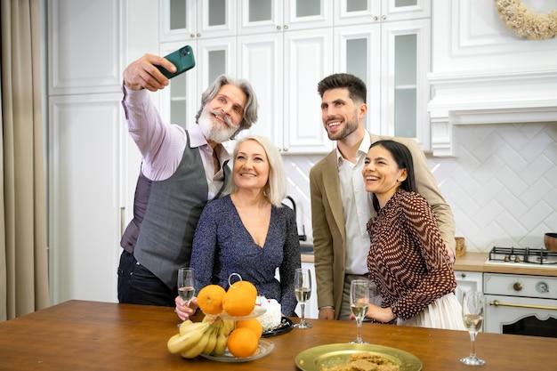 Avós de família felizes e jovem casal sorridente tirando uma selfie no smartphone