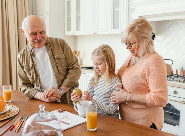 Avós de tiro médio e criança na cozinha