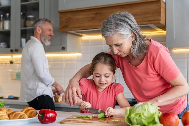 Avós de tiro médio e menina na cozinha