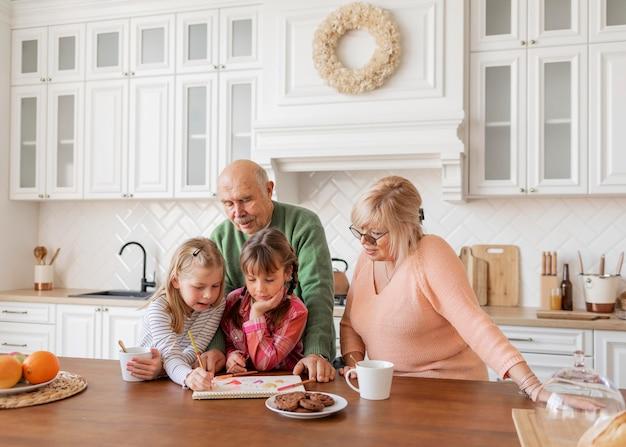 Avós de tiro médio e meninas na cozinha