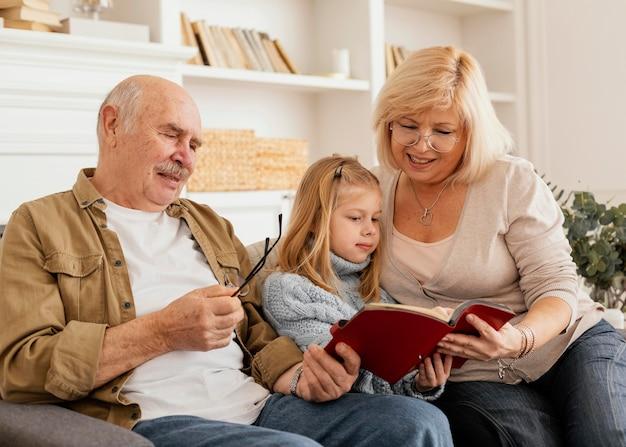 Avós de tiro médio lendo para criança