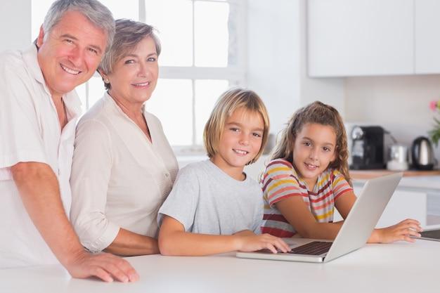 Avós e crianças olhando para a câmera junto com o laptop na frente
