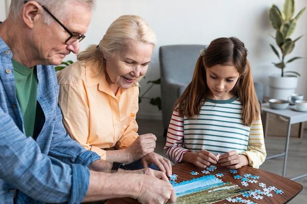 Avós e garota fazendo quebra-cabeça de perto