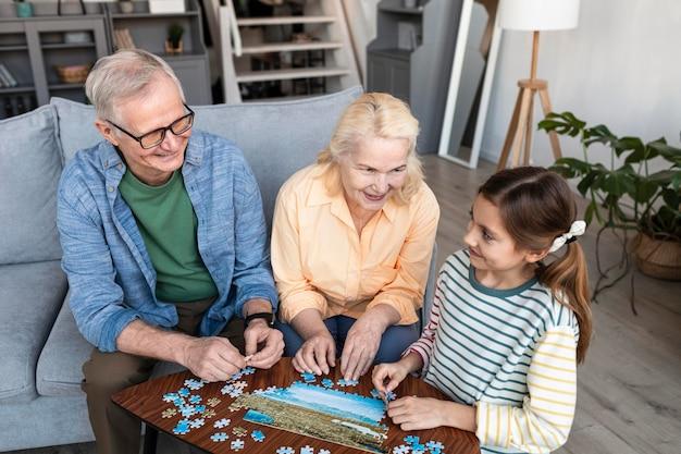 Avós e garota fazendo um quebra-cabeça médio