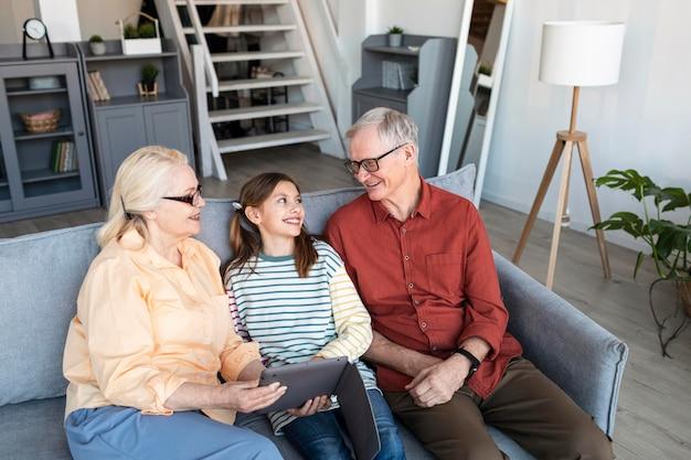 Avós e menina com laptop tiro médio