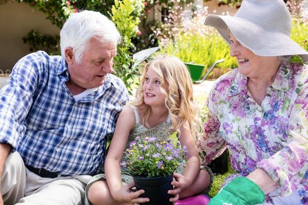 Avós e neta sentada no jardim
