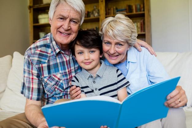 Avós e neto segurando um livro na sala de estar