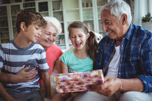 Avós e netos olhando surpresa presente na sala de estar