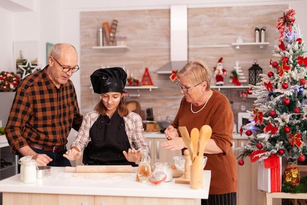Avós ensinando a neta a preparar pão de mel caseiro