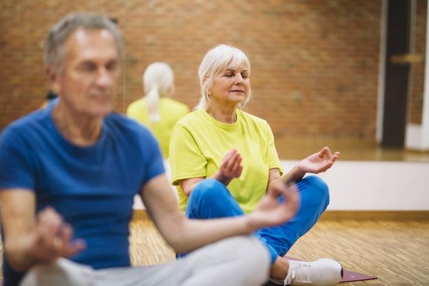 Avós fazendo yoga na academia