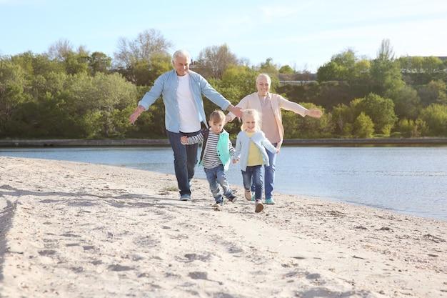 Avós felizes brincando com crianças pequenas na margem do rio