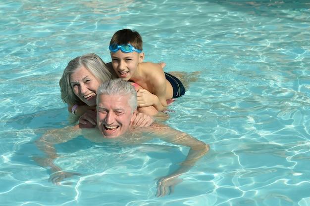 Avós felizes com o neto na piscina de férias