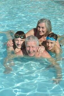 Avós felizes com os netos na piscina de férias