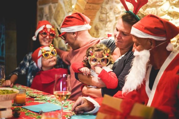 Avós, filhos, mãe, pai e irmã abrindo presentes de natal usando óculos engraçados e chapéus de papai noel