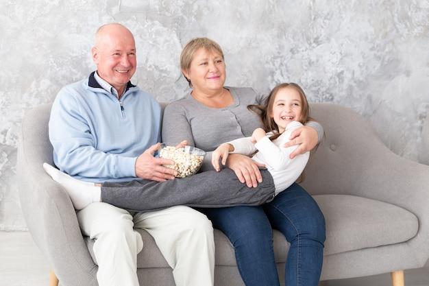 Avós, juntamente com neta assistindo tv, filme dentro de casa