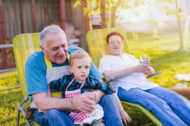 Avós se divertindo com seu neto, sentado no quintal e sorrindo.