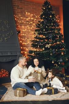 Avós sentados com a neta. comemorando o natal em uma casa aconchegante.