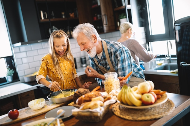 Avós sorridentes tomando café da manhã com a neta