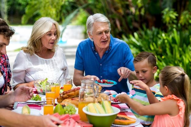 Avós tomando café da manhã com a família no quintal