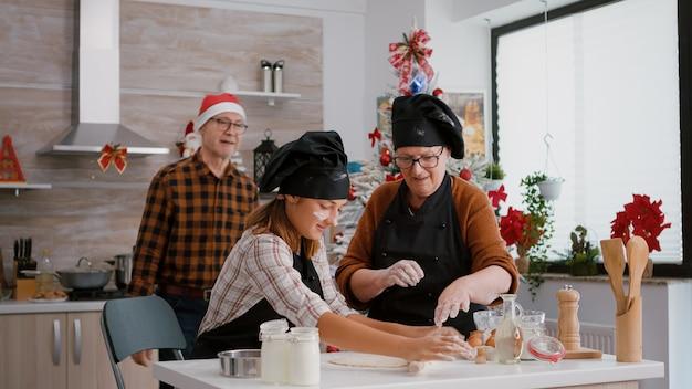 Avós tradicionais preparando sobremesas de biscoitos caseiros para comemorar o natal
