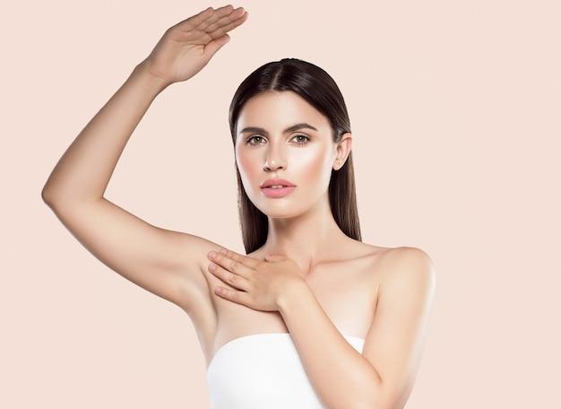 Axila entrega o conceito de desodorante de pele limpa de depilação de mulher. tiro do estúdio. cor de fundo.