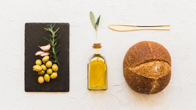 Azeite, alho e alecrim na placa de ardósia preta com óleo e pão integral em papel de parede branco