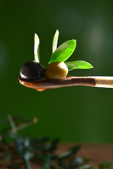 Azeite caindo sobre duas azeitonas com folhas de oliveira para dar sabor a uma salada mediterrânica.
