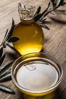 Azeite de oliva, folhas em uma mesa de madeira