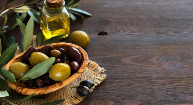 Azeite e azeitonas em fundo de madeira rústica