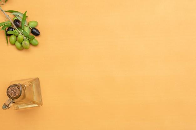 Azeite e ramo de oliveira em fundo laranja