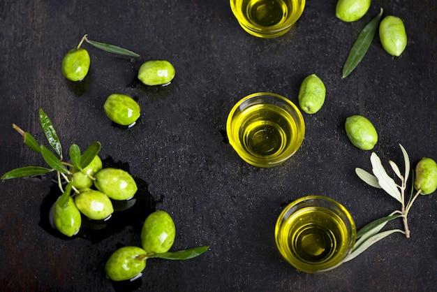 Azeite e ramo de oliveira em fundo preto.