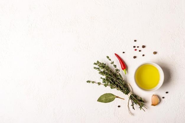 Azeite e um buquê de tomilho em um fundo de pedra branca
