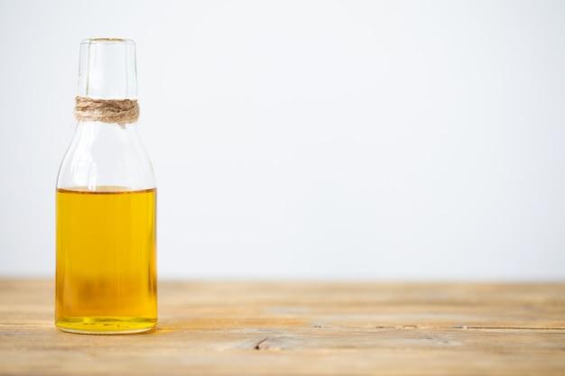 Azeite em uma garrafa sobre uma mesa de madeira com fundo branco. copie o espaço.