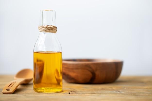 Azeite em uma garrafa, uma colher, um prato sobre uma mesa de madeira em um fundo branco. copie o espaço.