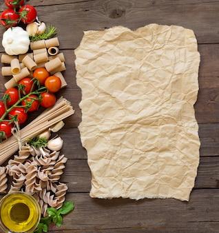 Azeite, macarrão, alho e tomate com papel artesanal na mesa de madeira, vista de cima com espaço de cópia