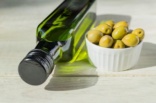 Azeite virgem extra em garrafa verde e azeitonas verdes frescas na mesa de madeira.