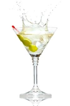 Azeitona espirrando no copo de martini isolado no branco