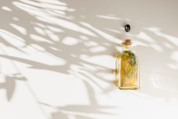 Azeitona preta sobre a garrafa de óleo na parede com sombra de folhas