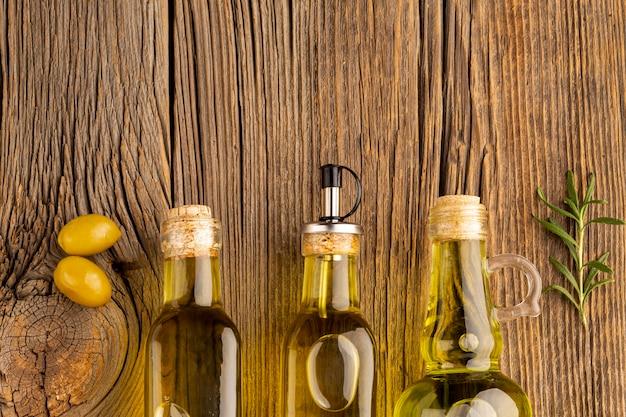 Azeitonas amarelas e frascos de óleo em fundo de madeira