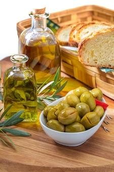 Azeitonas artesanais (enlatadas em azeite extra-virgem, vinagre, especiarias) com pimentão e alho. inclui folhas de árvores e uma garrafa de azeite extra-virgem. conceito de aperitivo.