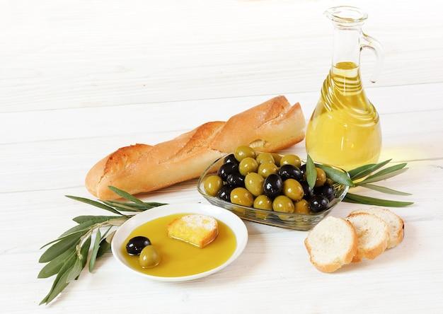 Azeitonas, azeite e pão, em uma mesa de madeira branca