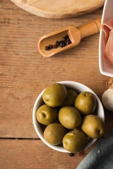 Azeitonas de alto ângulo e pimentos pretos na tábua