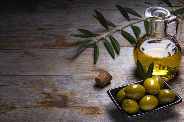 Azeitonas de aparência saborosa, azeite de oliva extra virgem e folhas de oliveira em fundo escuro de madeira